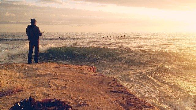 homme pêchant en bord de mer