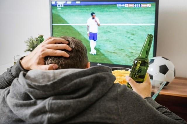 homme qui boit une biere devant la télévision